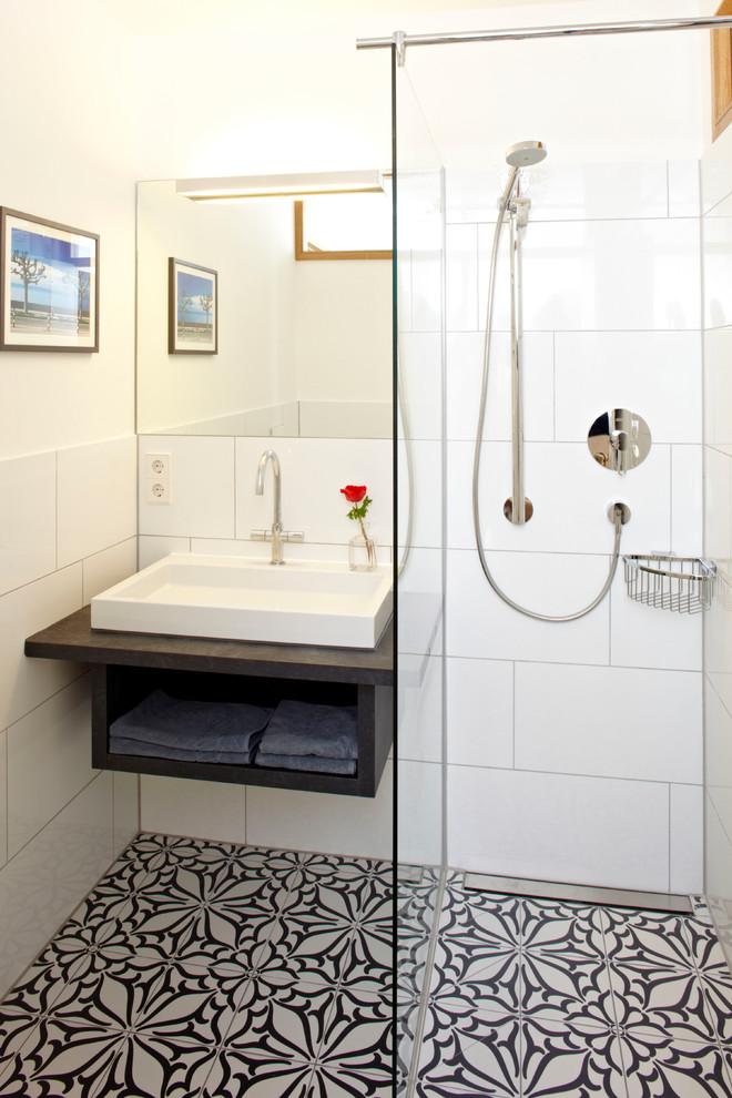 Kleines Klassisches Duschbad mit Aufsatzwaschbecken, weißer Wandfarbe, offenen Schränken, schwarzen Schränken, Eckdusche, weißen Fliesen, Keramikfliesen, Keramikboden, Quarzwerkstein-Waschtisch und buntem Boden in München