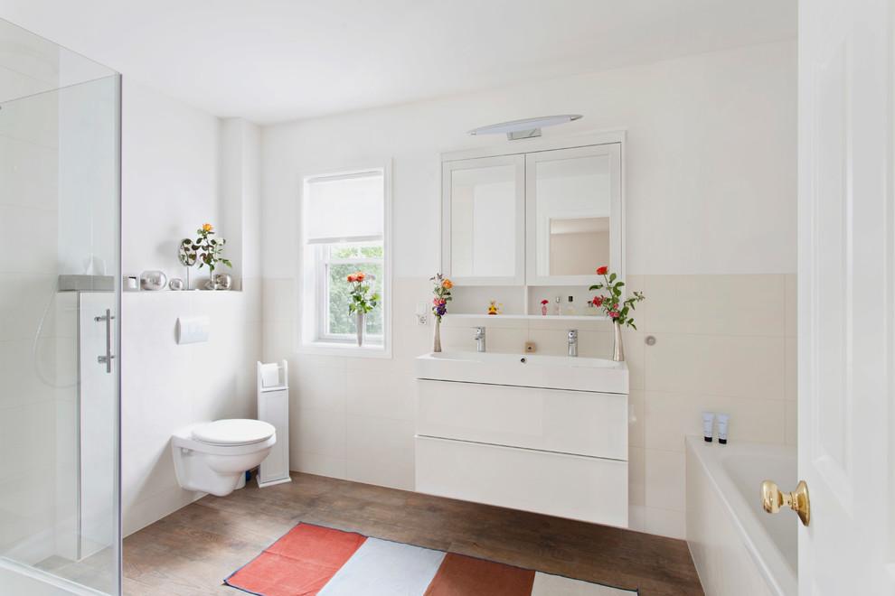 Foto di una stanza da bagno minimal di medie dimensioni con ante lisce, ante bianche, WC sospeso, piastrelle beige, pareti bianche, pavimento in legno massello medio, vasca da incasso, piastrelle in ceramica e lavabo rettangolare