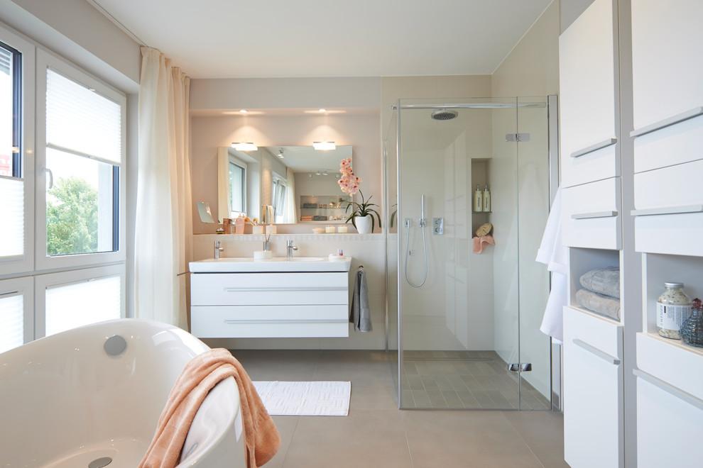 Großes Modernes Badezimmer mit flächenbündigen Schrankfronten, weißen Schränken, Eckdusche, beigefarbenen Fliesen, weißer Wandfarbe, freistehender Badewanne und integriertem Waschbecken in Sonstige