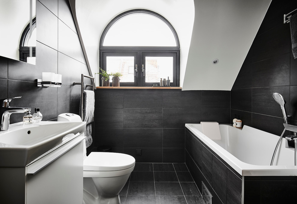 Inspiration for a large contemporary ceramic tile and black tile limestone floor and black floor tub/shower combo remodel in Gothenburg with flat-panel cabinets, white cabinets, an undermount tub, a one-piece toilet, black walls and an integrated sink