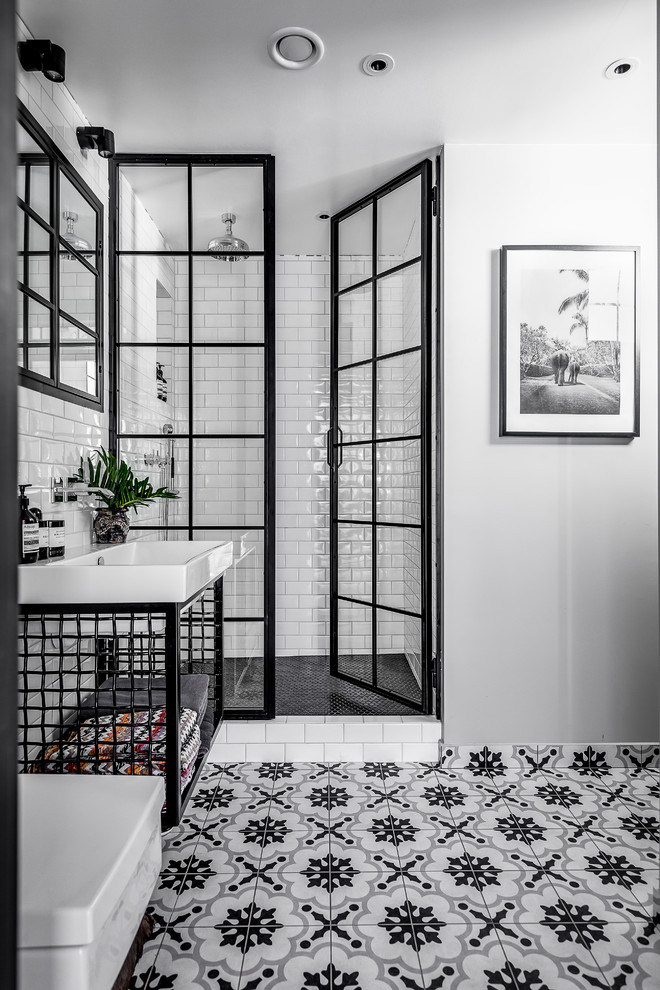 Example of a mid-sized urban white tile and subway tile ceramic tile and multicolored floor bathroom design in Stockholm with open cabinets, black cabinets, white walls, a drop-in sink and a hinged shower door