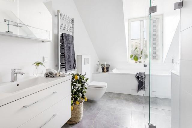 Ejemplo de cuarto de baño nórdico, de tamaño medio, con armarios con paneles lisos, puertas de armario blancas, ducha esquinera, paredes blancas, sanitario de pared, baldosas y/o azulejos blancos, suelo de piedra caliza, lavabo integrado y bañera encastrada
