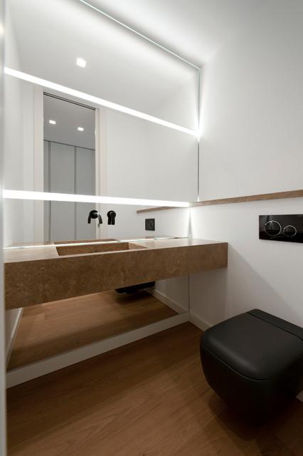 Idee per un bagno di servizio minimalista con pareti bianche, pavimento in legno massello medio, lavabo integrato e top beige