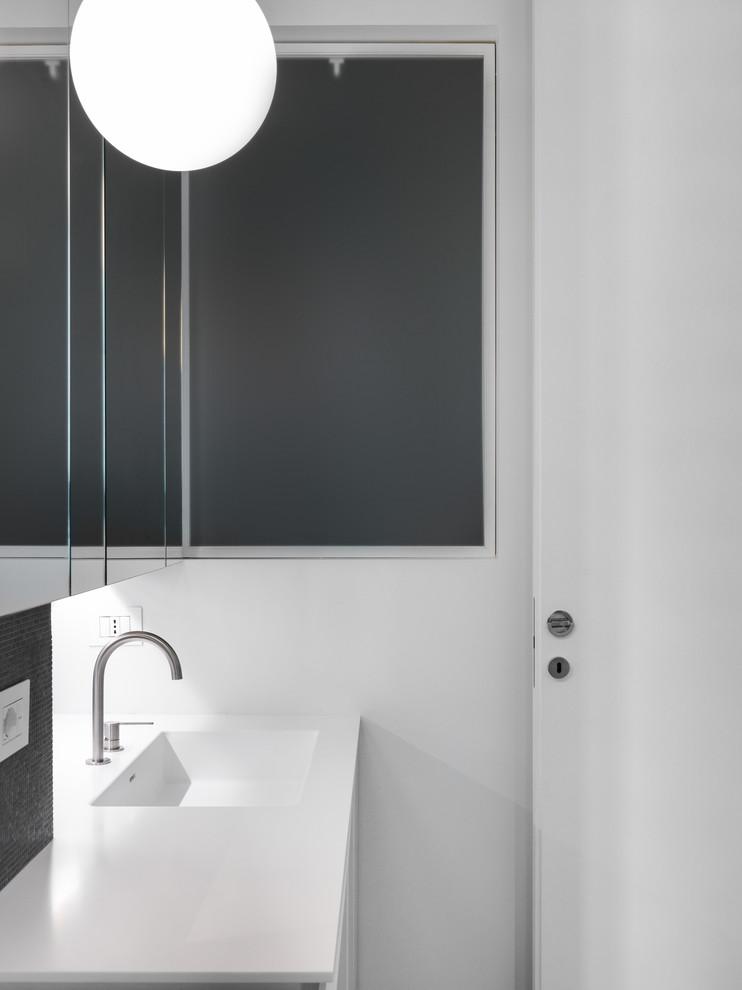 Immagine di un bagno di servizio minimalista di medie dimensioni con ante lisce, ante bianche, WC a due pezzi, piastrelle nere, piastrelle di vetro, pareti nere, pavimento in legno massello medio, lavabo integrato, top in superficie solida e top bianco
