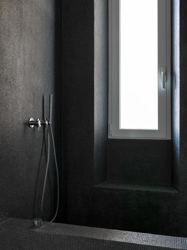 Esempio di un bagno di servizio minimalista di medie dimensioni con WC a due pezzi, piastrelle nere, piastrelle di vetro, pareti nere, pavimento in cemento e pavimento grigio