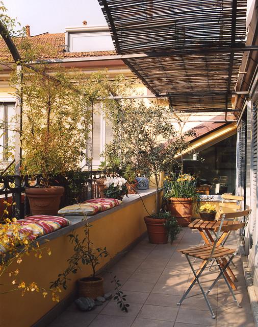 Esempio di piccoli terrazze e balconi country con un giardino in vaso e un parasole