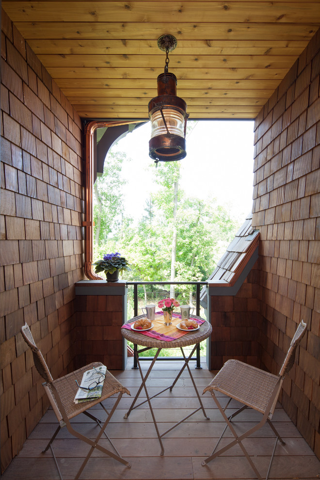 Inspiration for a rustic balcony remodel in Minneapolis with a roof extension