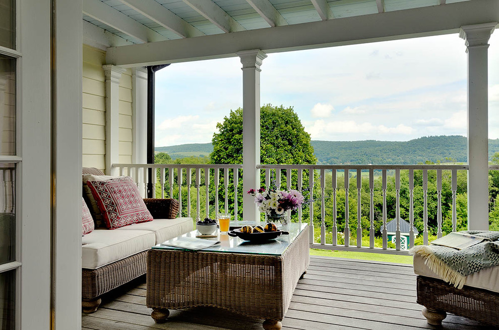 Example of a cottage balcony design in New York with a roof extension