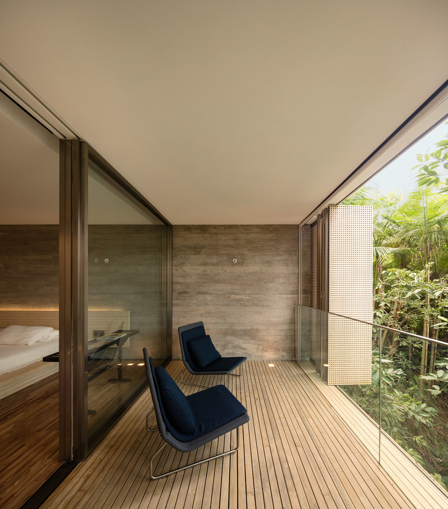 Example of a huge minimalist privacy balcony design in Other with a roof extension