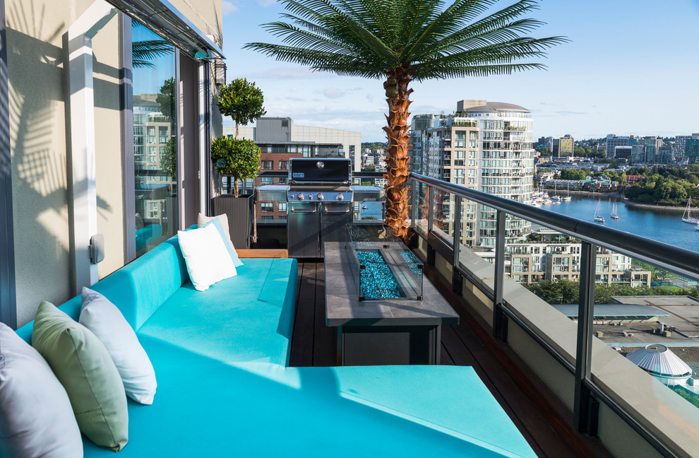 Small beach style glass railing balcony photo in Vancouver with a fire pit