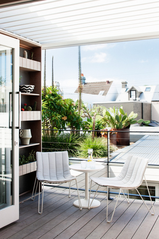 Example of a small trendy balcony design in Sydney with a pergola