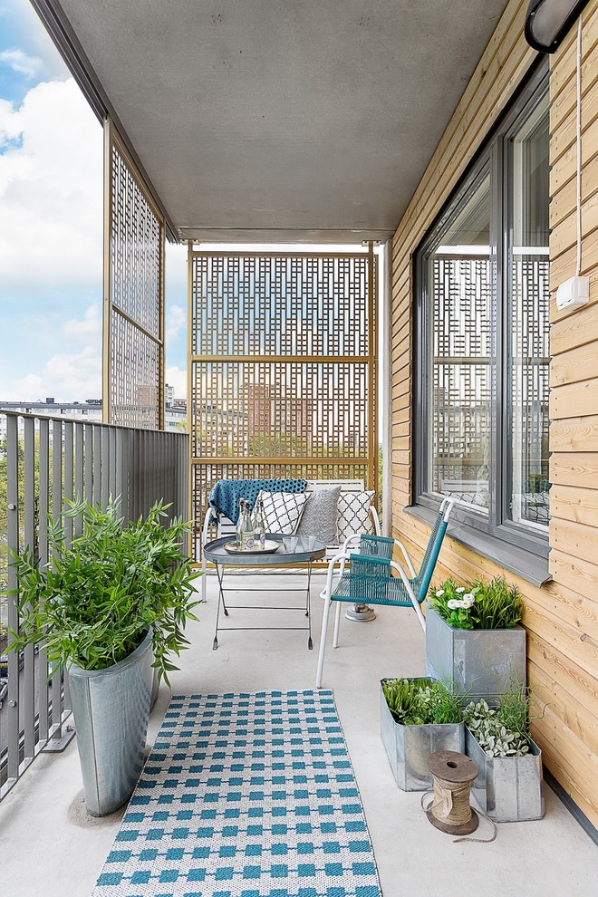 Inspiration for a mid-sized scandinavian privacy balcony remodel in Stockholm with a roof extension