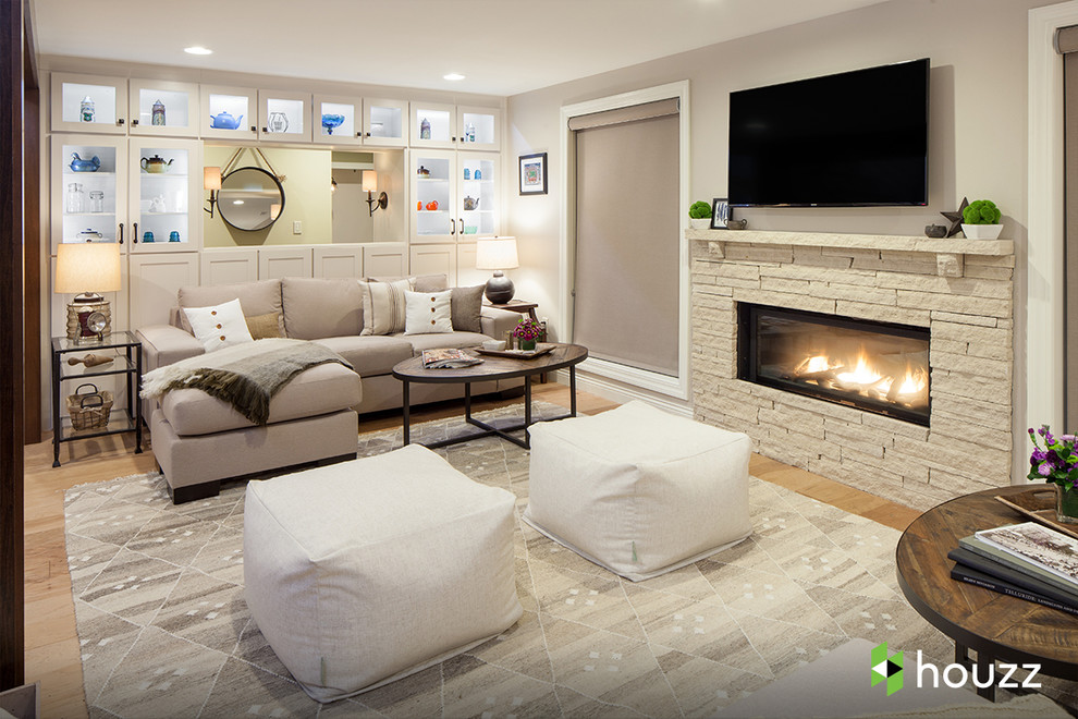 Elegant walk-out light wood floor and beige floor basement photo in Other with gray walls and a ribbon fireplace