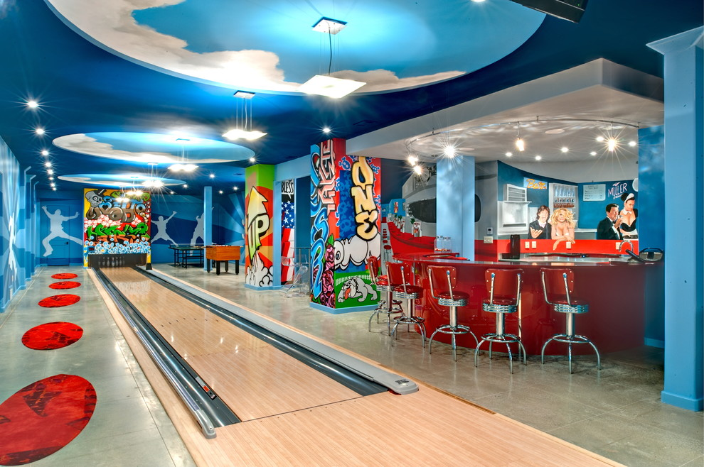 Trendy underground concrete floor basement game room photo in Atlanta with blue walls and no fireplace