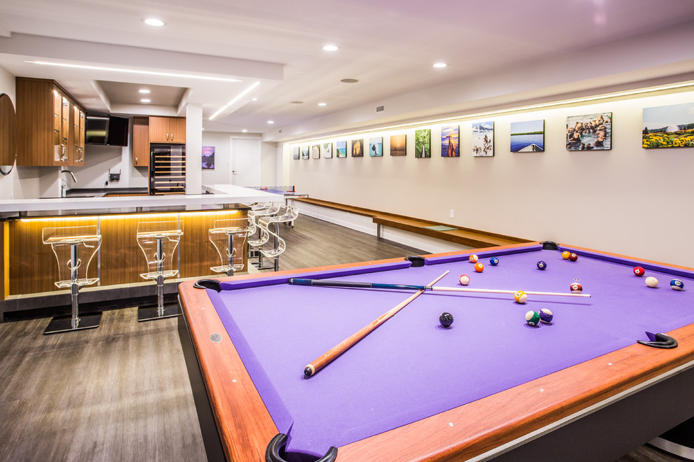 Basement game room - large modern underground dark wood floor and brown floor basement game room idea in New York with beige walls and no fireplace