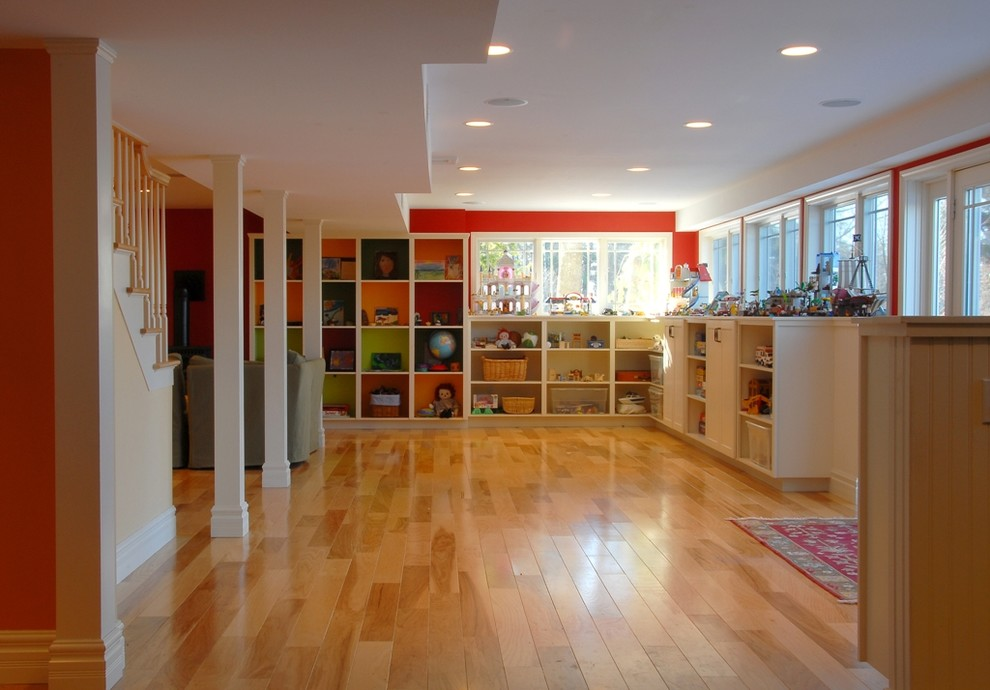 Example of a classic look-out light wood floor and orange floor basement design in Burlington with red walls