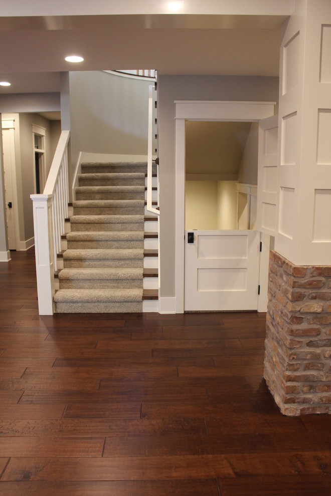 Example of a large transitional walk-out dark wood floor basement design in Salt Lake City with gray walls, a standard fireplace and a stone fireplace