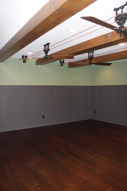 Example of a large transitional walk-out medium tone wood floor basement design in Salt Lake City with gray walls, a standard fireplace and a stone fireplace