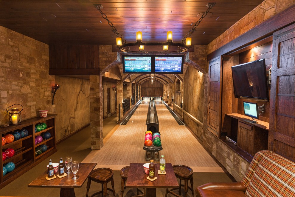 Basement game room - huge rustic underground basement game room idea in Milwaukee with brown walls and no fireplace