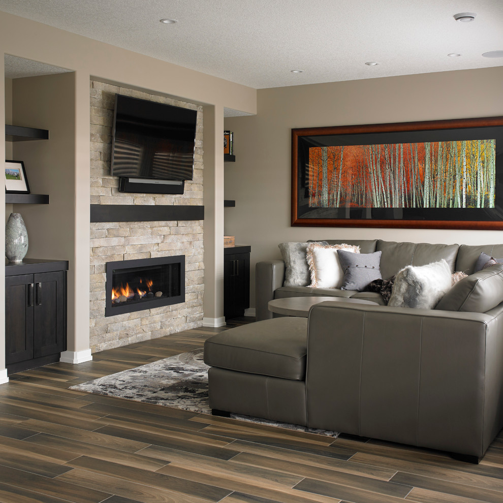 Inspiration for a transitional ceramic tile basement remodel in Calgary with beige walls, a standard fireplace and a stone fireplace