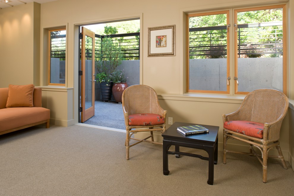 Trendy walk-out carpeted and gray floor basement photo in Seattle with beige walls