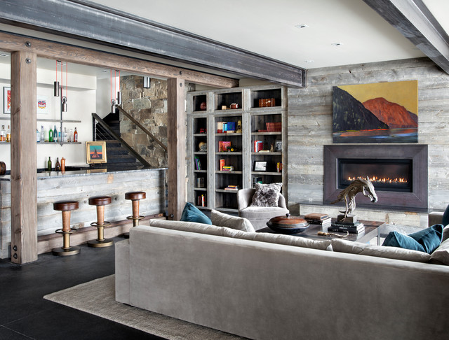 Basement - rustic black floor basement idea in Other with beige walls, a wood fireplace surround and a ribbon fireplace