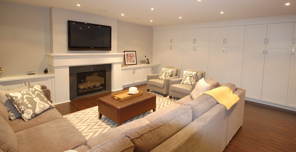 Example of a large transitional look-out dark wood floor basement design in Toronto with beige walls, a standard fireplace and a stone fireplace