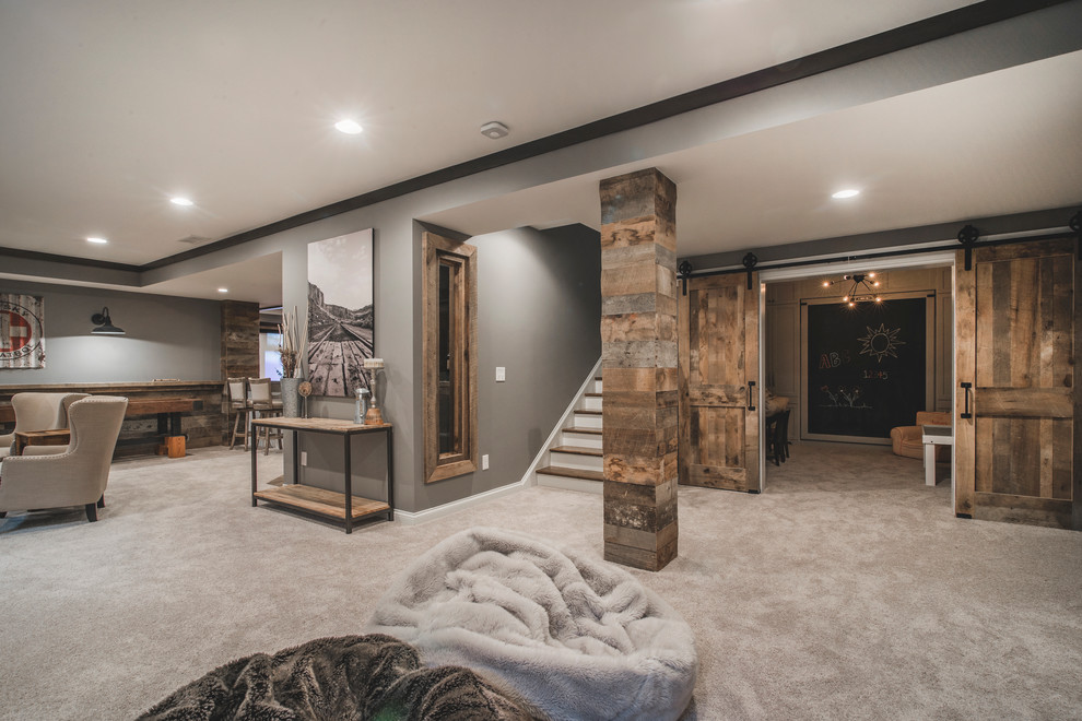 Example of a large mountain style look-out carpeted and gray floor basement design in Columbus with gray walls