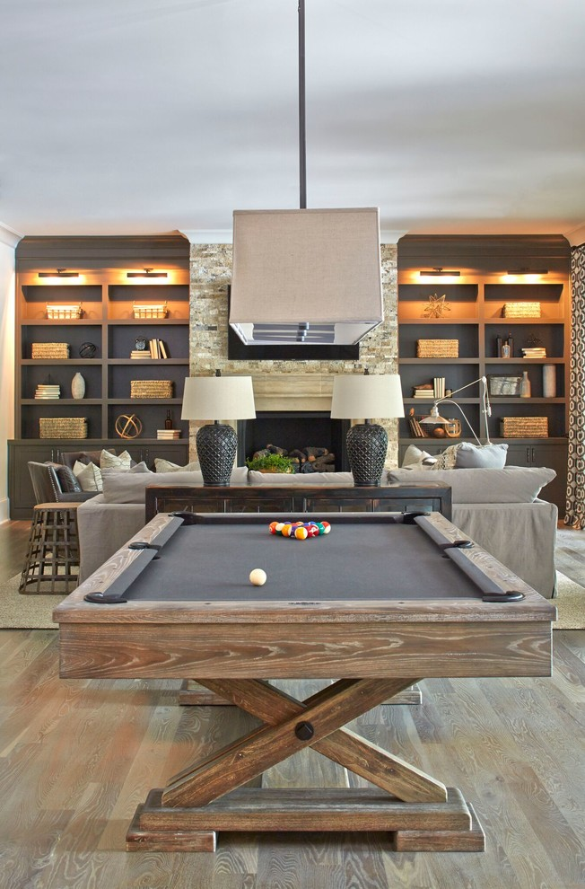 Example of a huge country walk-out medium tone wood floor basement design in Atlanta with white walls and a standard fireplace
