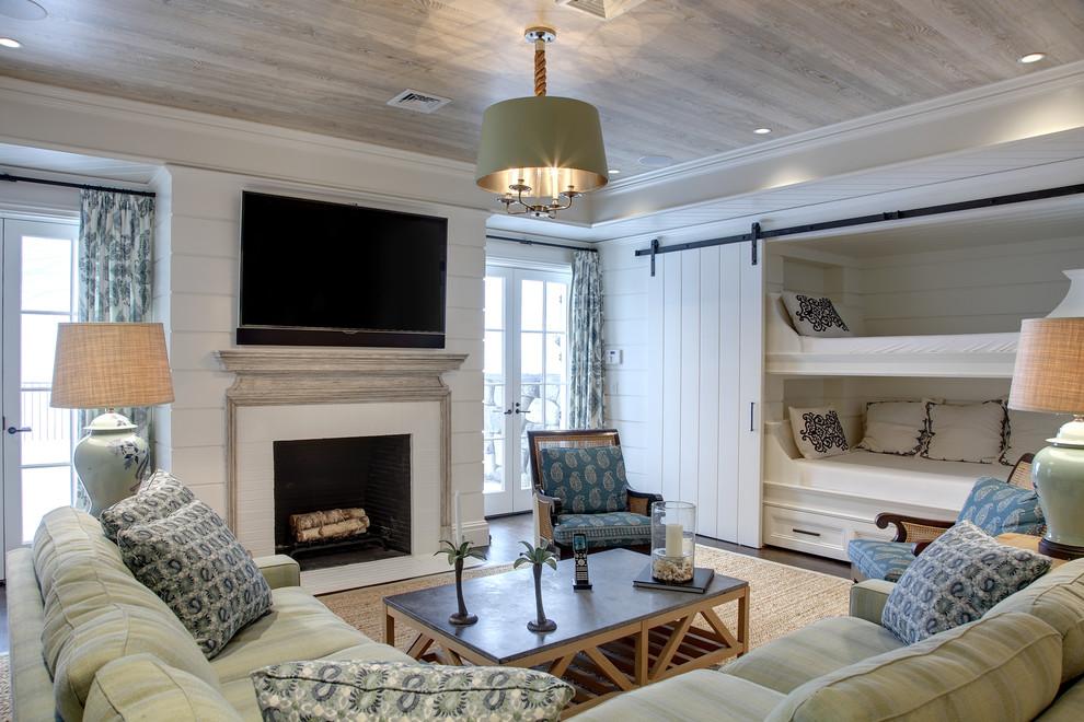 Cette photo montre un sous-sol bord de mer donnant sur l'extérieur et de taille moyenne avec un mur blanc, un sol en bois foncé, une cheminée standard et un sol marron.