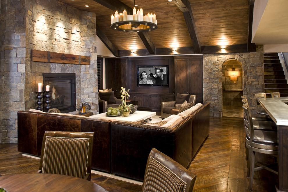 Example of a mountain style underground dark wood floor basement design in Minneapolis with a stone fireplace and a standard fireplace