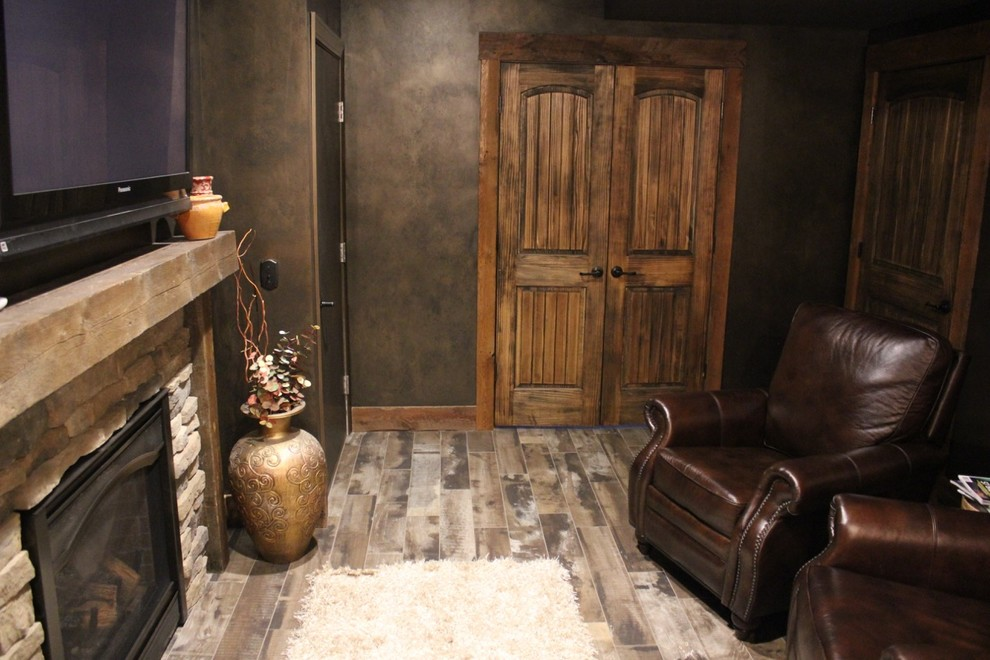 Basement - mid-sized craftsman underground medium tone wood floor and gray floor basement idea in Boston with a standard fireplace, a stone fireplace and black walls