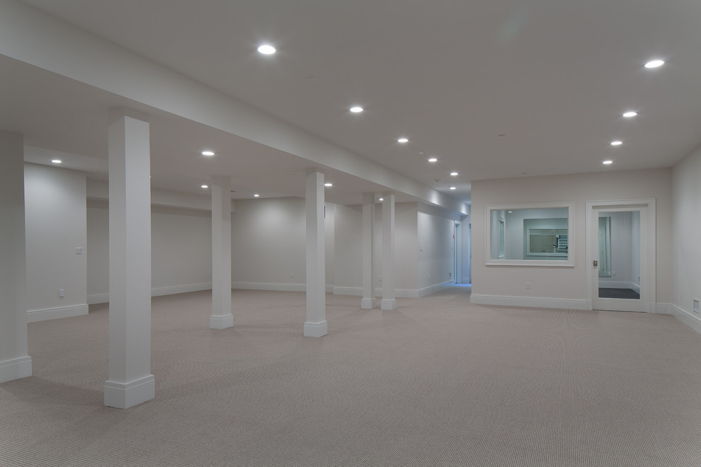 Example of a large transitional underground carpeted basement design in New York with gray walls and no fireplace