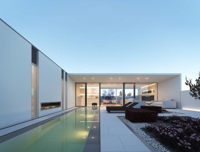 Cette image montre une grande piscine arrière design rectangle avec un bain bouillonnant et des pavés en pierre naturelle.