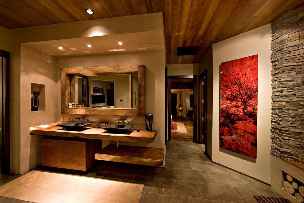 Trendy beige tile bathroom photo in Las Vegas with a vessel sink, flat-panel cabinets, medium tone wood cabinets and wood countertops