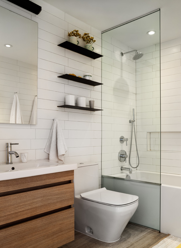Example of a small trendy kids' white tile gray floor bathroom design in New York with flat-panel cabinets, a one-piece toilet, white walls, medium tone wood cabinets and a console sink