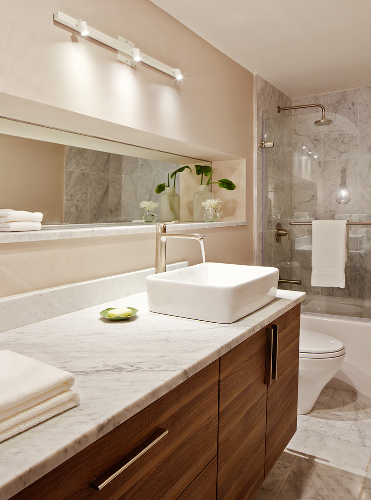 Bathroom - mid-sized contemporary master stone tile and white tile marble floor bathroom idea in San Francisco with a vessel sink, flat-panel cabinets, dark wood cabinets, marble countertops, a one-piece toilet and beige walls