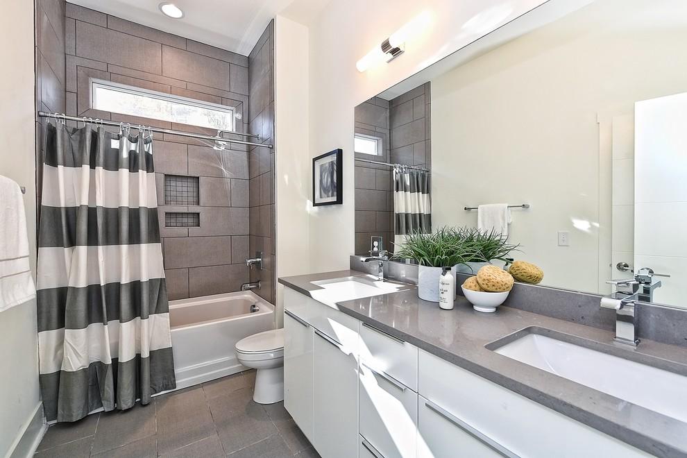 Foto de cuarto de baño clásico renovado con armarios con paneles lisos, puertas de armario blancas, bañera empotrada, combinación de ducha y bañera, baldosas y/o azulejos grises, paredes blancas, aseo y ducha, lavabo bajoencimera, suelo gris, ducha con cortina y encimeras grises