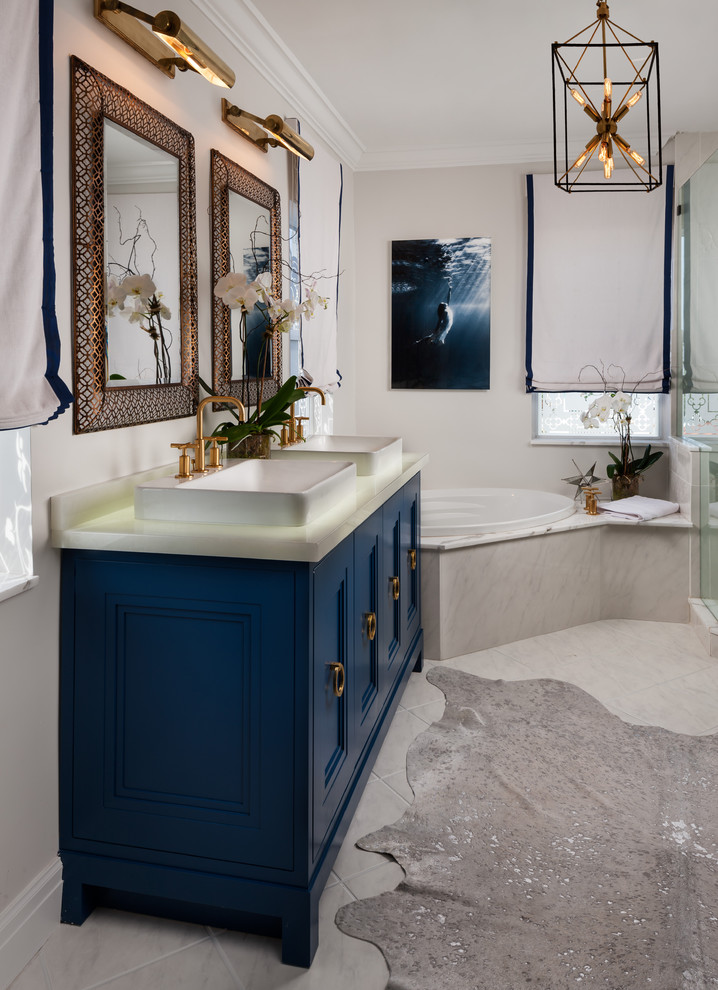Example of a mid-sized transitional master marble floor drop-in bathtub design in Miami with a vessel sink, furniture-like cabinets, blue cabinets and gray walls