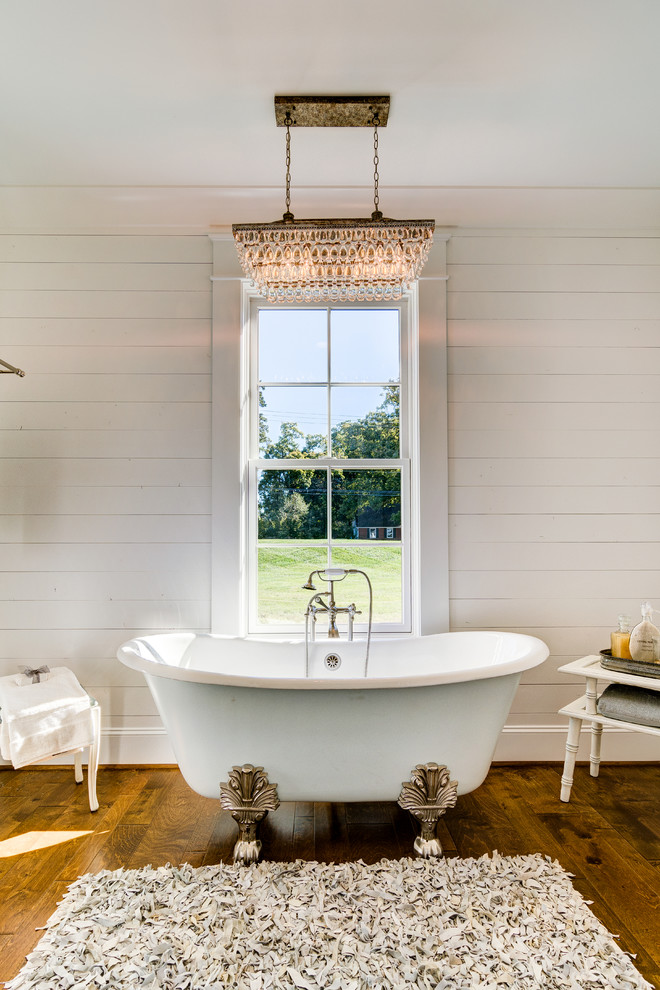 Large farmhouse medium tone wood floor and brown floor claw-foot bathtub photo in Other with white walls