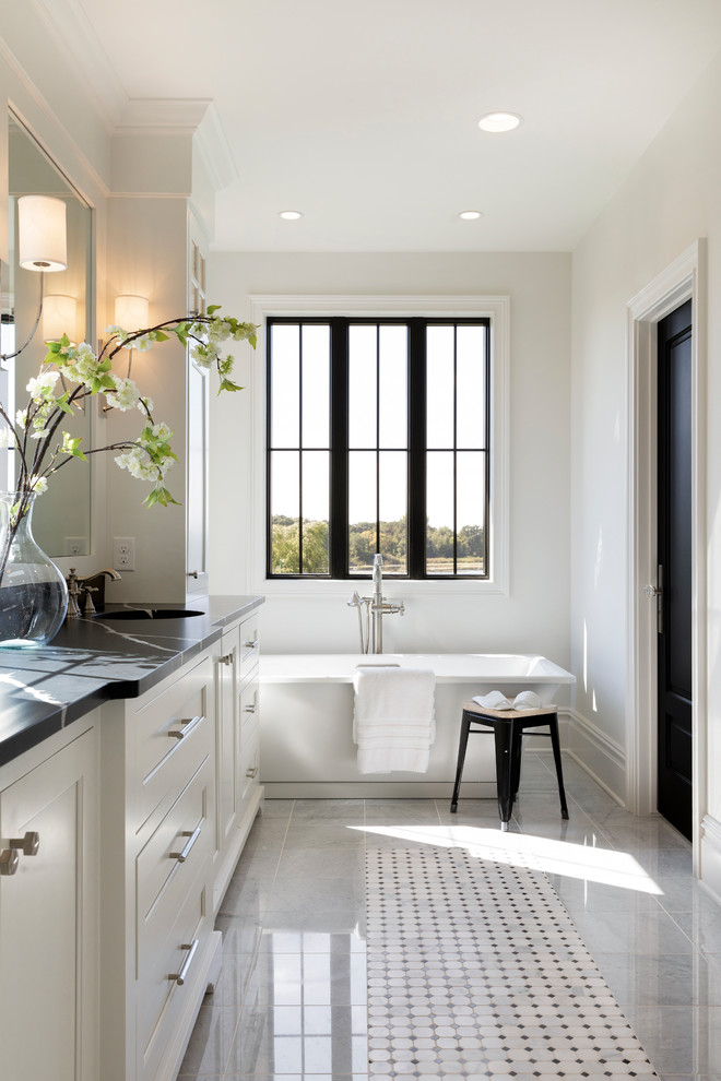Freestanding bathtub - country mosaic tile floor and white floor freestanding bathtub idea in Minneapolis with recessed-panel cabinets, white cabinets, white walls, an undermount sink and black countertops