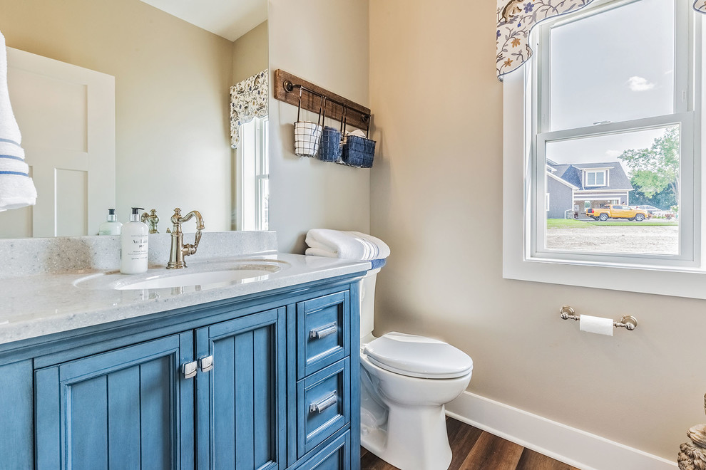 Small 3/4 medium tone wood floor and brown floor bathroom photo in New York with furniture-like cabinets, blue cabinets, a one-piece toilet, beige walls, an undermount sink, quartz countertops and gray countertops