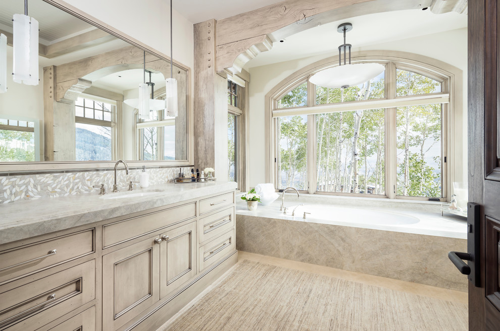 Inspiration for a huge rustic gray tile and mosaic tile beige floor bathroom remodel in Salt Lake City with beige cabinets, marble countertops, recessed-panel cabinets, an undermount tub, white walls, an undermount sink and gray countertops