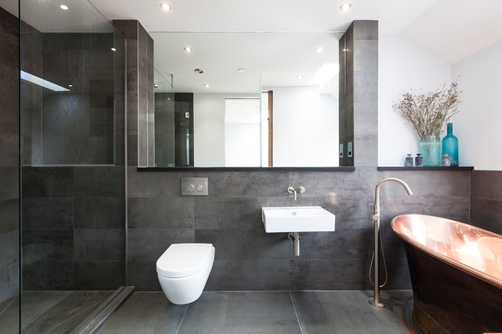 Trendy gray tile bathroom photo in London with a wall-mount sink, a wall-mount toilet and white walls
