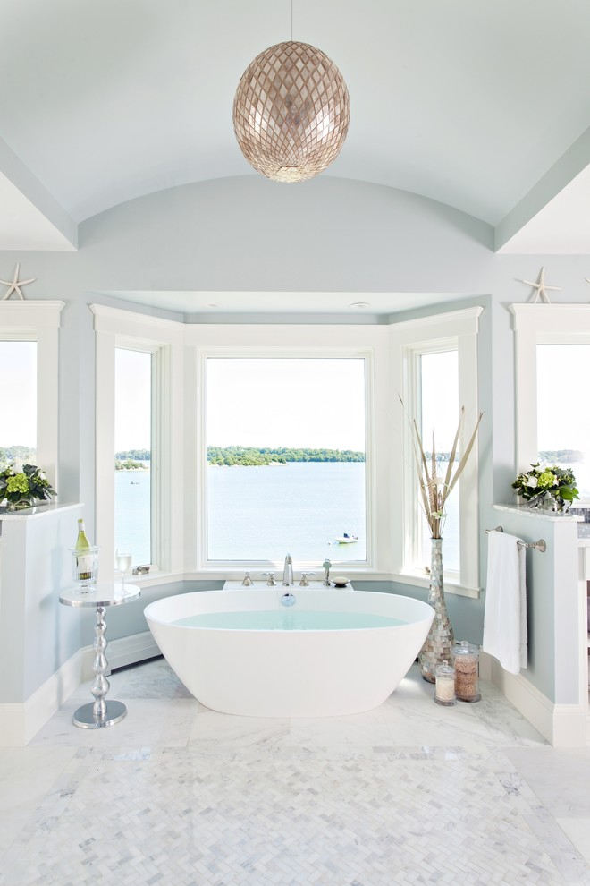 Example of a beach style master mosaic tile and white tile freestanding bathtub design in Boston with blue walls
