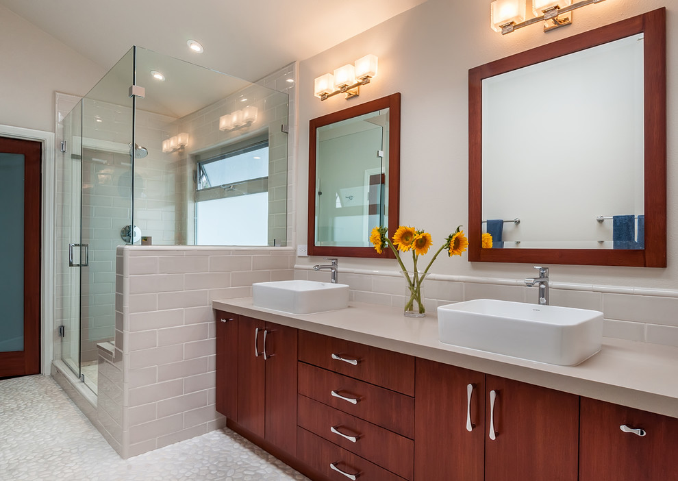 Inspiration for a large modern master beige tile and porcelain tile pebble tile floor and beige floor double shower remodel in Los Angeles with flat-panel cabinets, medium tone wood cabinets, a one-piece toilet, beige walls, a vessel sink, quartz countertops and a hinged shower door