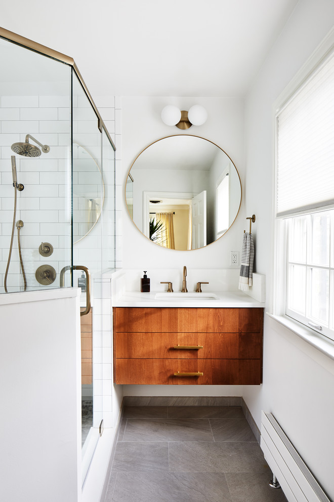 Corner shower - small contemporary white tile gray floor corner shower idea in DC Metro with flat-panel cabinets, medium tone wood cabinets, white walls, an undermount sink, a hinged shower door and white countertops