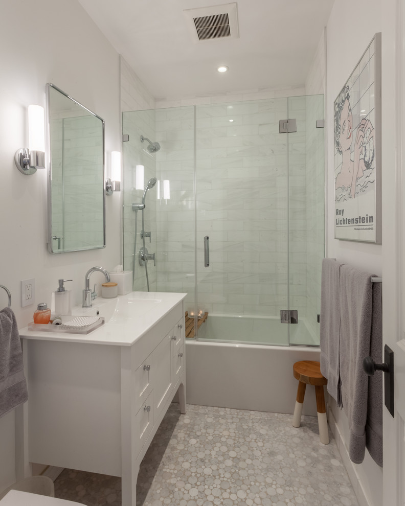 Bathroom - transitional 3/4 white tile and marble tile mosaic tile floor and gray floor bathroom idea in Chicago with furniture-like cabinets, white cabinets, white walls, an integrated sink, a hinged shower door and white countertops