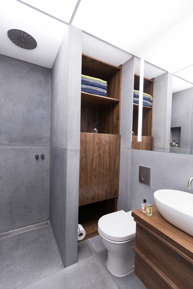 Bathroom - mid-sized contemporary 3/4 gray tile and cement tile concrete floor bathroom idea in London with a vessel sink, flat-panel cabinets, dark wood cabinets, wood countertops, a wall-mount toilet, gray walls and brown countertops