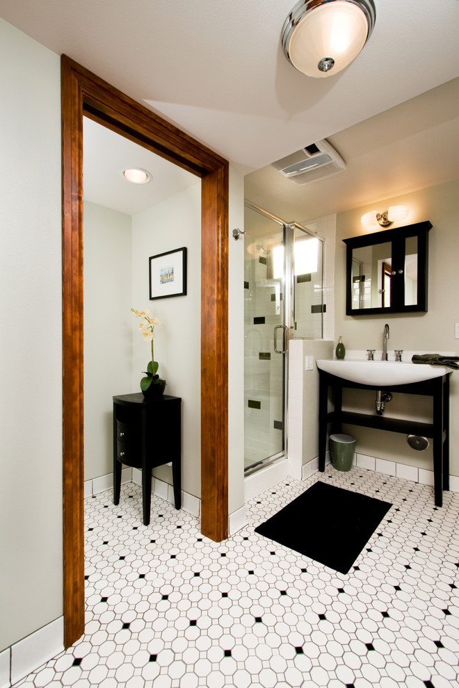 Example of a trendy black and white tile multicolored floor corner shower design in Denver with a console sink